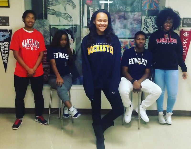 Five students proudly wearing their college sweatshirts