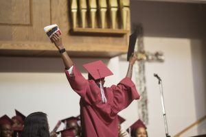 Student in graduation robes riases hands in the air, back turned to audience