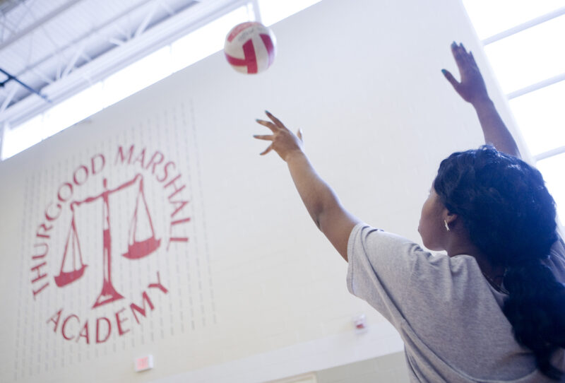 A volleyball player prepares to spike the ball, with TMA logo on the wall in front of her.