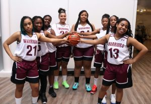 Members of the girls basketball team, standing in a V shape with all players holding a basketball.